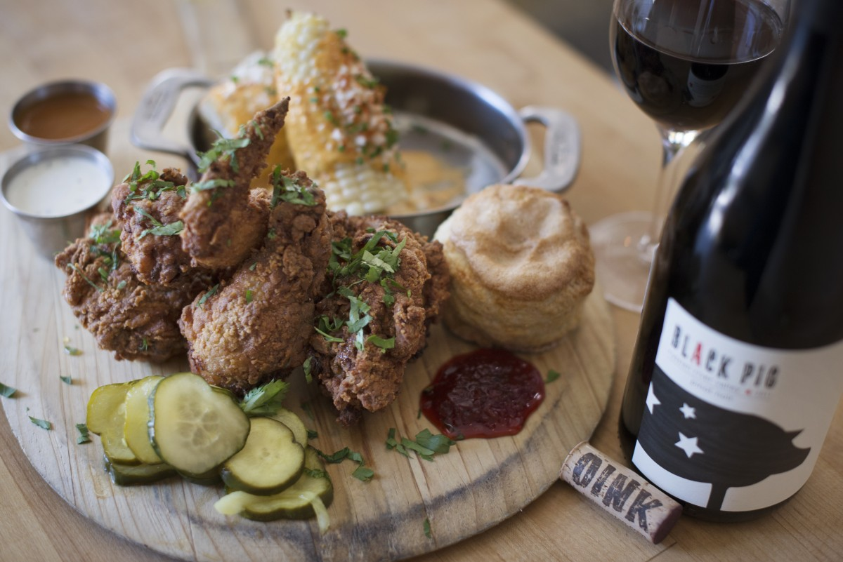 A bottle of Black Pig pinot noir to accompany buttermilk fried Petaluma chicken with fiscalini cheddar biscuit, red pepper jelly and elote at zazu kitchen + farm in The Barlow in Sebastopol, California. June 18, 2016. (Photo: Erik Castro/for Sonoma Magazine)