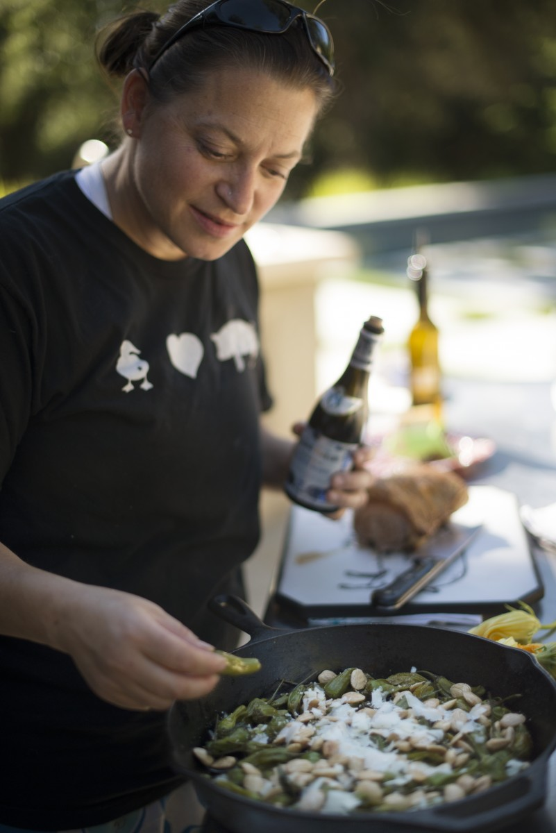 Duskie Estes tasting her wood-fired roasted shishito peppers with Marcona almonds and shavings of Pennyroyal Farm Boont Corners cheese alongside an arugula salad at her home in Forestville, California. June 18, 2016. (Photo: Erik Castro/for Sonoma Magazine)