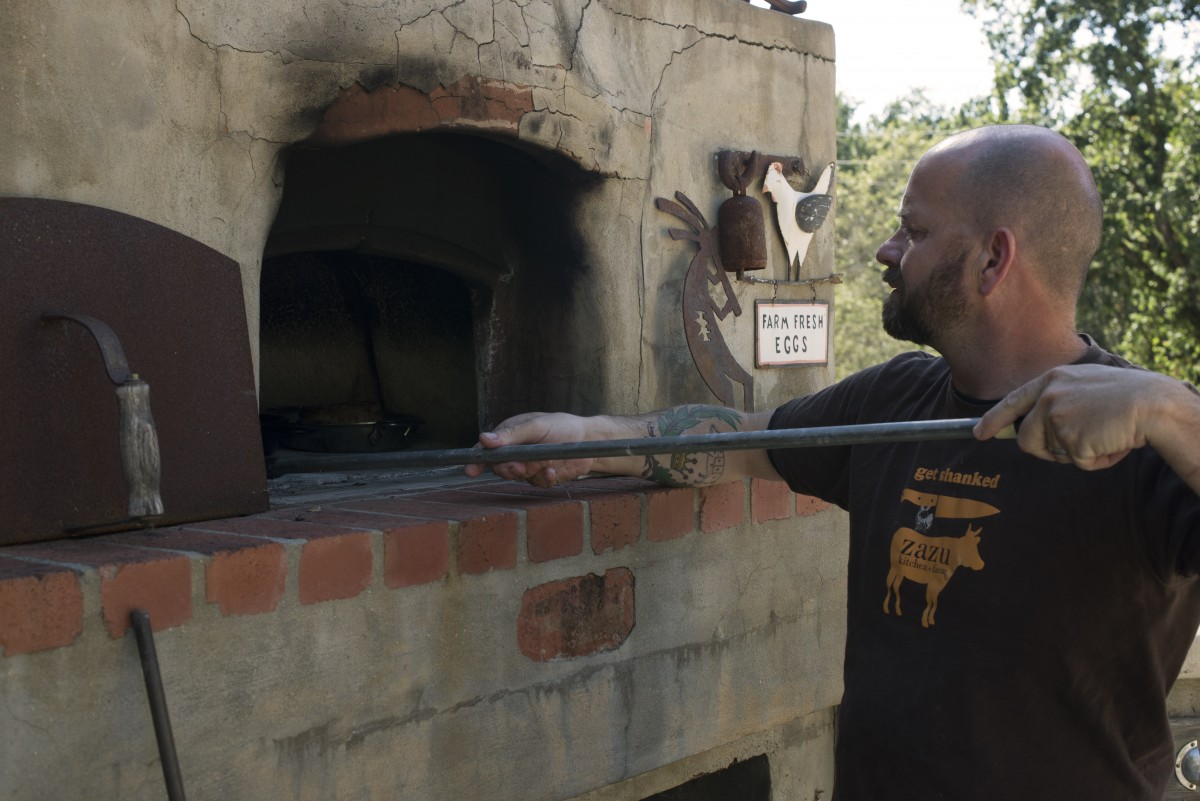 John Stewart cooking with his wood-fired oven at his home in Forestville, California. June 18, 2016. (Photo: Erik Castro/for Sonoma Magazine)