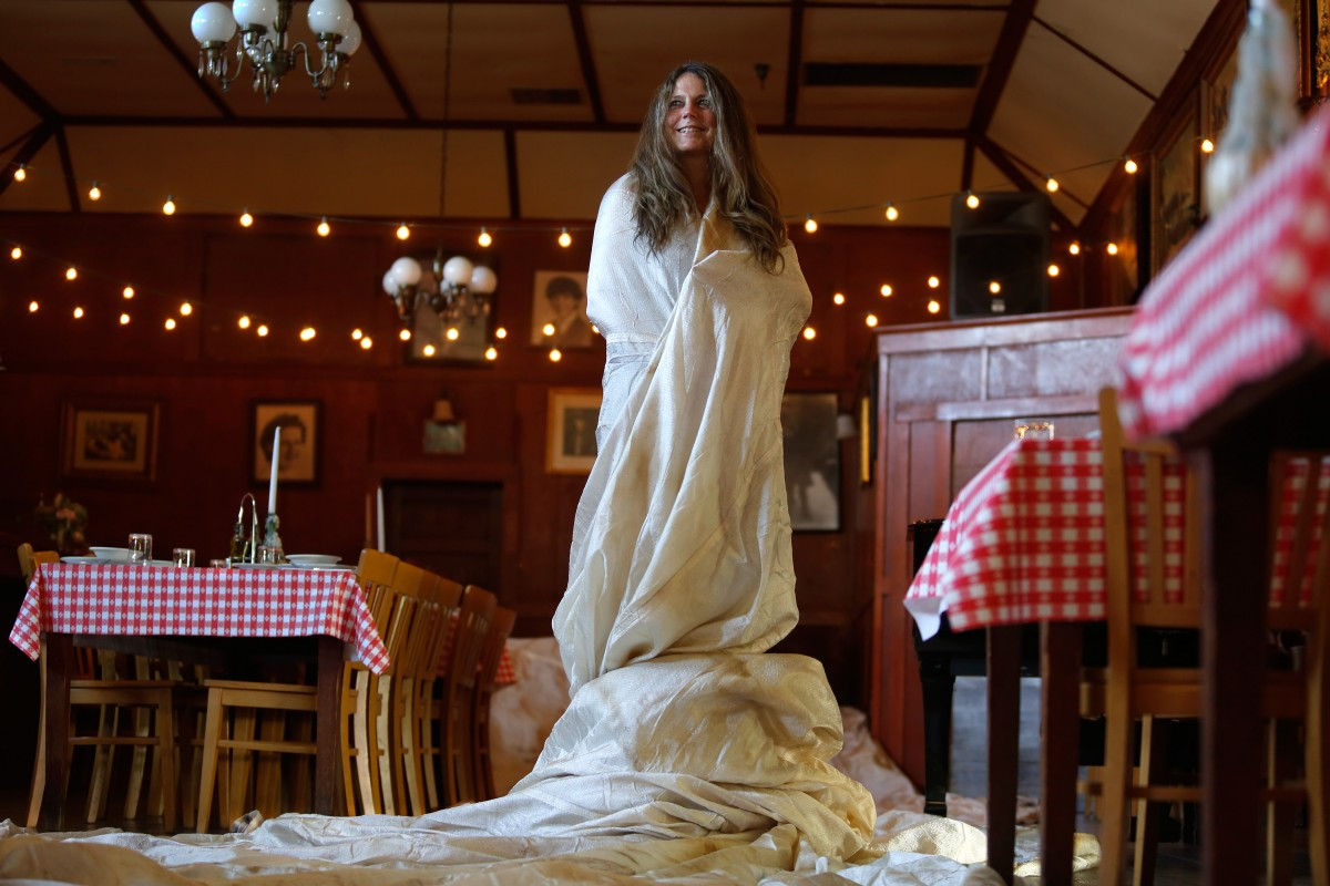 At her Union Hotel Restaurant in Occidental, Barbara Gonnella wraps herself in one of the 2,050 panels of white nylon fabric Christo used in his art installation. (Photo by Alvin Jornada)