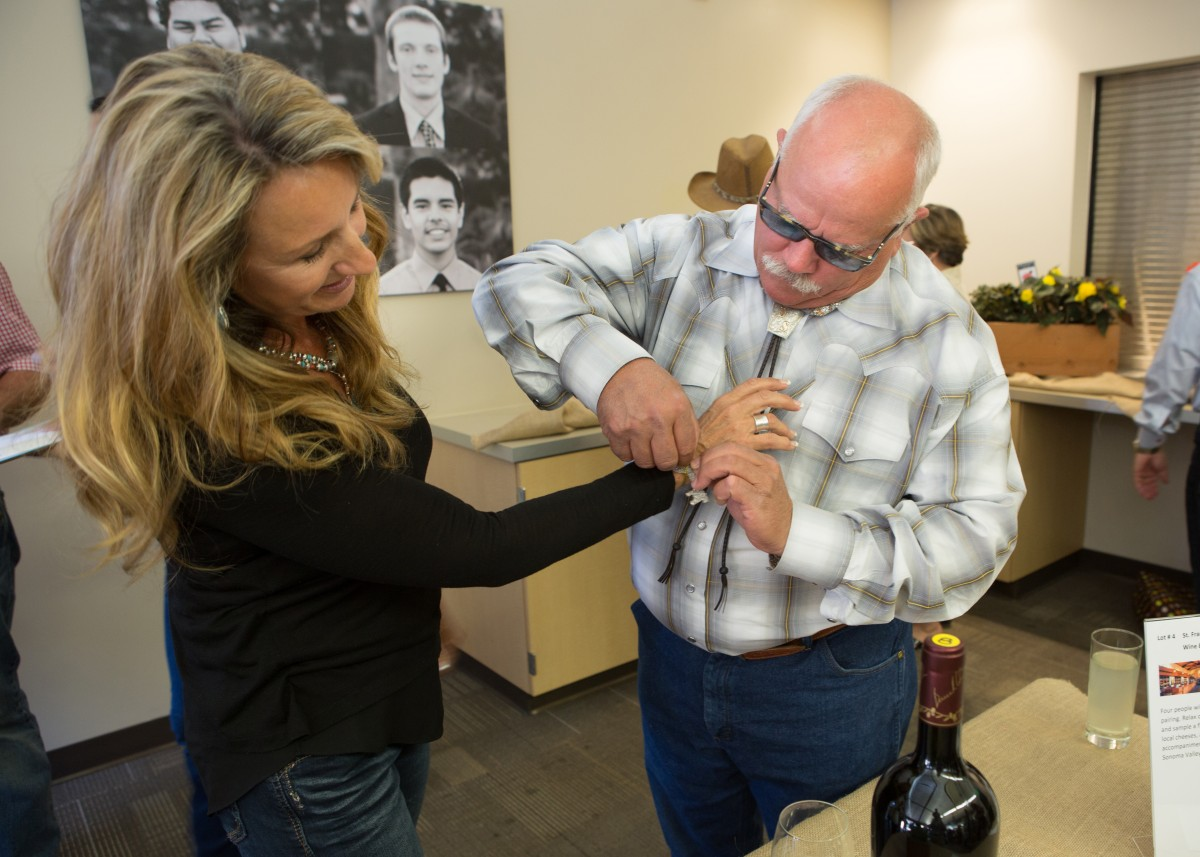 Kristi Steadman of Novato gets at $50 fundraising key tied to her wrist by her husband Dan. The winning key will open a cabine stockt wih wine.