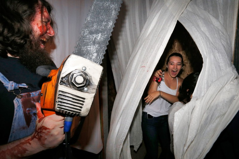 Chainsaw-weilding actor Nate Friedman, left, emerges from behind a curtain to scare Kaitlyn Bradley and her friends in the Slaughter Shack at Blind Scream Haunted House, in Rohnert Park, California on Wednesday, October 19, 2016. (Alvin Jornada / The Press Democrat) Blind Scream Haunted House