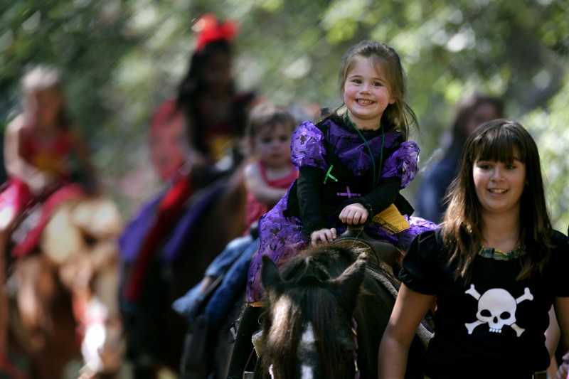 Dressed as a witch for a Halloween bash at Howarth Park in Santa Rosa on Saturday, 3-year-old Bella Pena enjoys her ride on a Pony Express horse. In addition to pony rides, the fifth annual party offered ice cream, candy and plenty of fun.