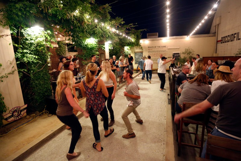 Players dance on the court after finishing their game during bocce league play at Campo Fina restaurant in Healdsburg, California on Thursday, July 14, 2016. (Alvin Jornada / The Press Democrat)
