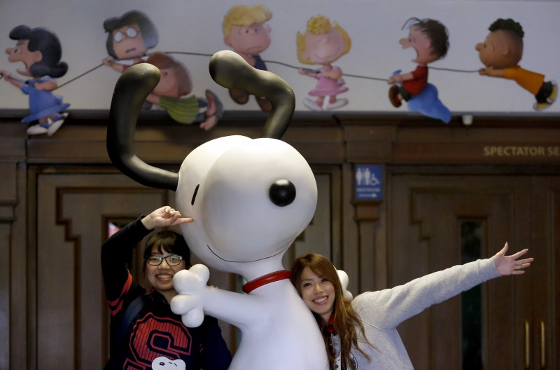 Chisa Tatsumi, left, and Sakiko Yazawa, tourists from Japan, pose as their friend, Yuka Shimada, takes their photo with Snoopy at the Redwood Empire Ice Arena in Santa Rosa, on Wednesday, November 4, 2015. (BETH SCHLANKER