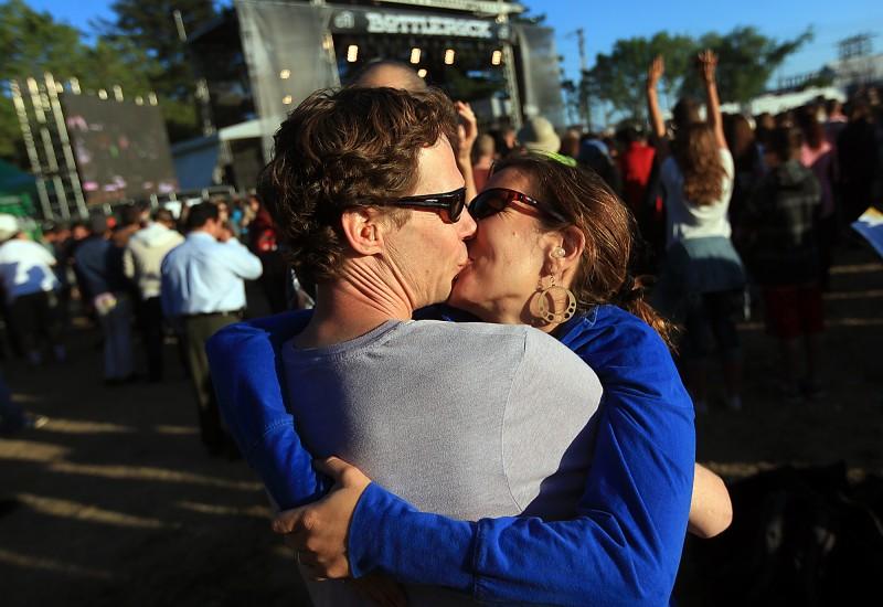 Lia Gaertner gives her boyfriend Sunjya Schweg a smooch on his 40th birthday at BottleRock in Napa, Thursday May 9, 2013. They are both from Sebastopol. (Kent Porter / Press Democrat) 2013