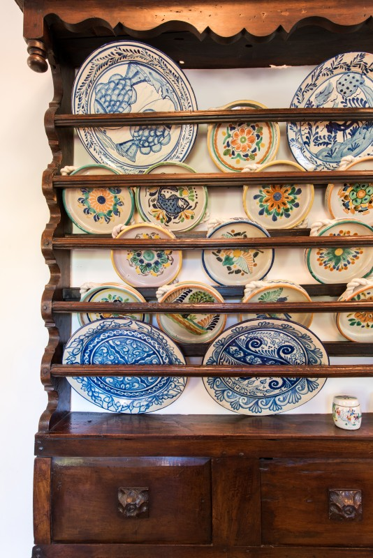 An antique dish rack is filled with cherished plates.