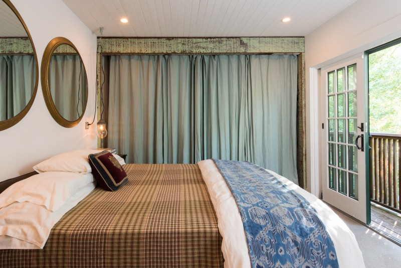 The master bedroom with sliding French doors that open to the view.