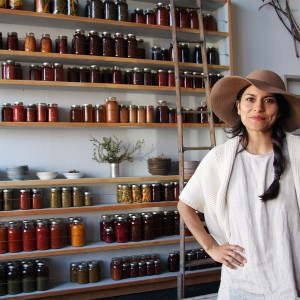 Dalia Martinez of Flower and Bone in front of their wall of preserves. Heather Irwin/PD