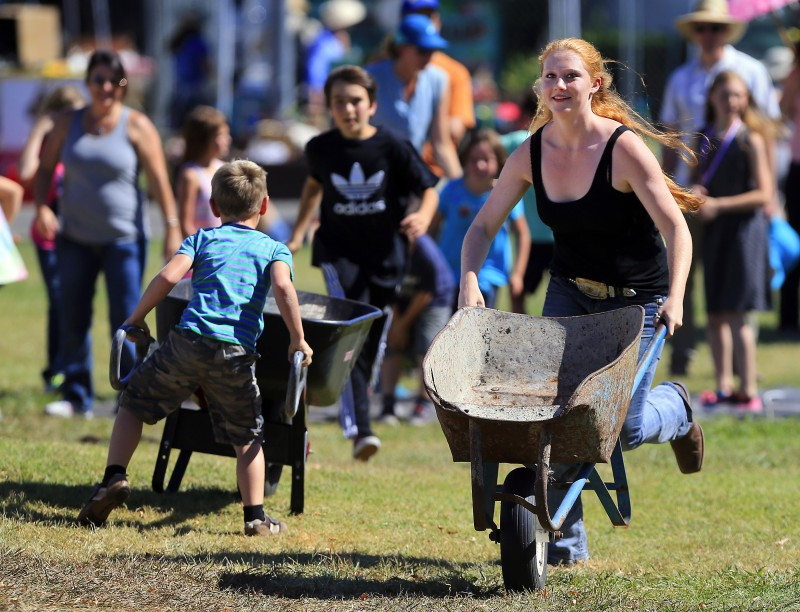 Ariel Scholten takes the lead for the girls in the Compost Wheelbarrow race at the Farmer Olympics at the Petaluma Fairgrounds on Saturday. (John Burgess