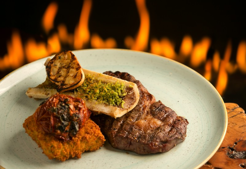 Grilled Creekstone 21 day Dry Aged Rib Eye Steak with Summer Ratatouille, Panelle and Roasted Bone Marrow at the Coast Kitchen in the newly remodeled Timber Cove Lodge on the Sonoma Coast. (John Burgess/The Press Democrat)