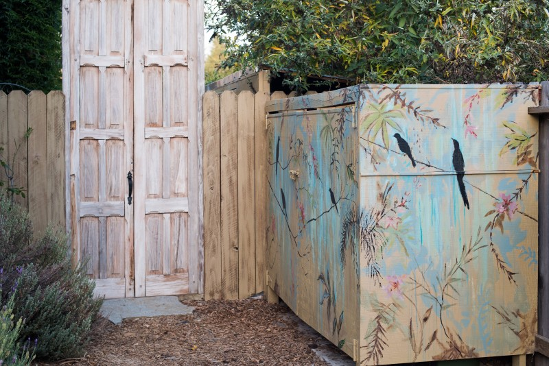 he birds and lowers that decorate a storage shed are painted in subtle colors that blend with nature.