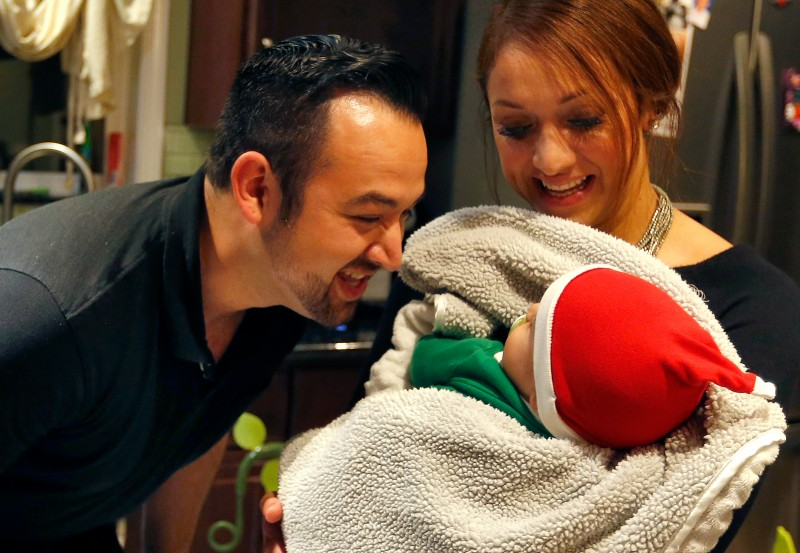 Sal Chavez, left, and his wife Kina play with their eight-month-old son Maximus at their home in Sonoma, California, on Wednesday, November 30, 2016. (Alvin Jornada