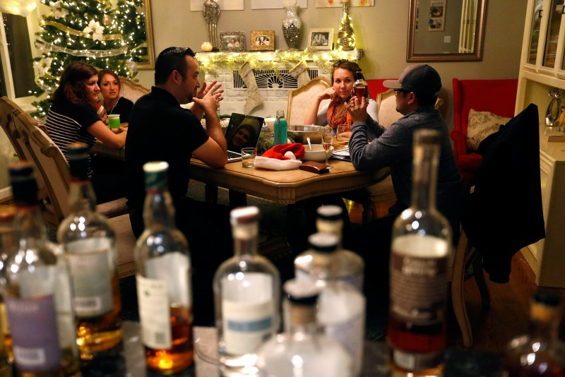 Sal Chavez, left, talks about a bottle of bourbon with his friend and business partner Aiki Terashima as they taste a variety of liquor at Chavez's home in Sonoma, California, on Wednesday, November 30, 2016. Pictured from left are: Swiss exchange student Alexia Raccio who is staying with the Chavez's, Kina Chavez, Sal Chavez, Hillary Terashima and Aiki Terashima. (Alvin Jornada / The Press Democrat)