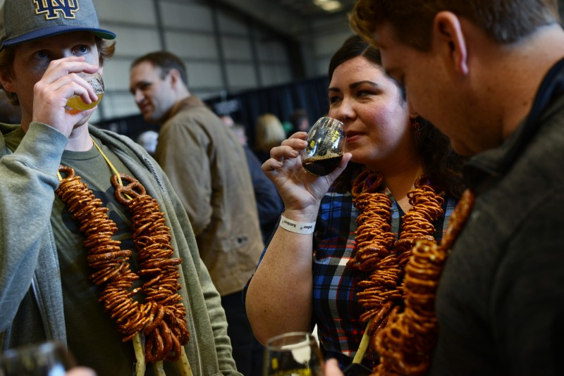 Attendees from left, Tim Redmond, of Los Angeles, Daniel Lyons, of Orange County and Brook Phelps, of Los Angeles, during RateBeer Best International Beer Festival held at Kaiser Air Inc. private hangar Sunday in Santa Rosa, California. January 31, 2016. (Photo: Erik Castro/for The Press Democrat)