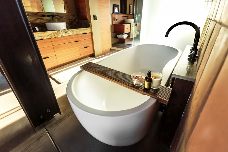 The curving standalone tub in the master bath has a saltillo tile backsplash and looks out to the hills