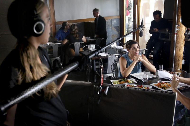 "Actress Dorian Brown preps for a scene as boom operator Corryn Deegan checks the sound during filming of the movie ""Running Wild"" at the The Pullman Kitchen in Santa Rosa, on Monday, August 17, 2015. (BETH SCHLANKER/"