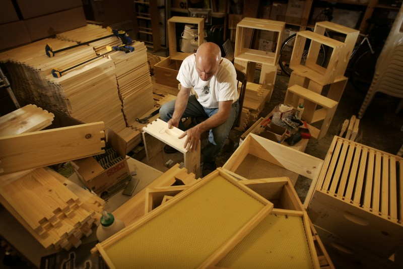 Doug Vincent, owner of Beekind, builds bee boxes in his Sebastopol store for the apples and asian pears at Gabriel Farms. Each box will be stocked with 10,000 bees contained in the screened box. photo by John Burgess