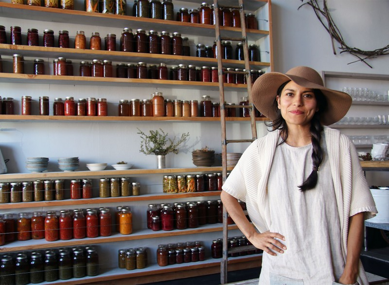 Dalia Martinez of Flower and Bone in front of their wall of preserves. Heather Irwin