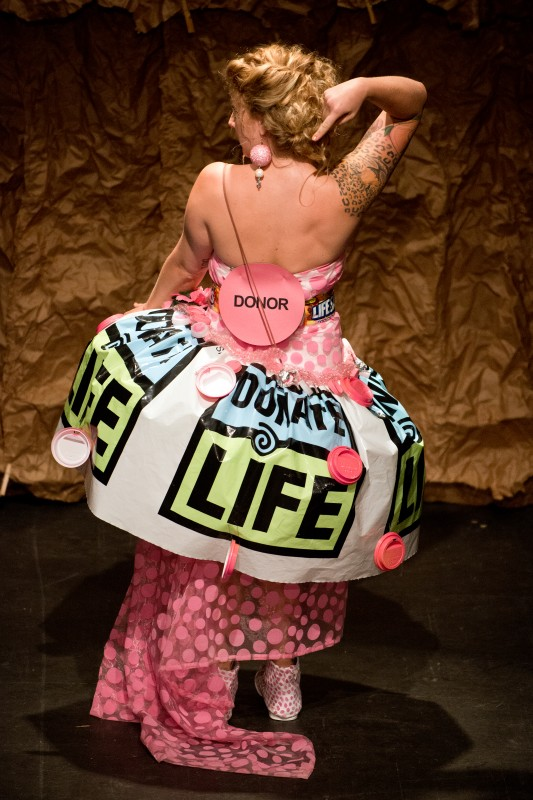 "Model Kelly Rose Gibbons wears designer Marcy Waldron's ""Recycle Yourself! Be an Organ Donor"" dress, made of a plastic table cloth, candy wrappers and plastic cup lids painted pink to represent the donor dot on a driver's license, during the Trashion Fashion Show, where designers create outfits out of recycled materials, at the Sonoma Community Center in Sonoma, Calif., on April 26, 2013. (Alvin Jornad"