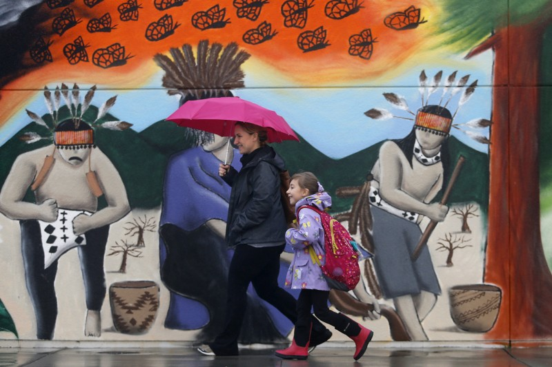 A student and parent walk past a mural that was painted over a wall that had been spray painted with anti-immigrant messages and Donald Trump's name. Photo taken before the start of school at Cali Calmecac Language Academy in Windsor, on Friday, January 20, 2017. (BETH SCHLANKER