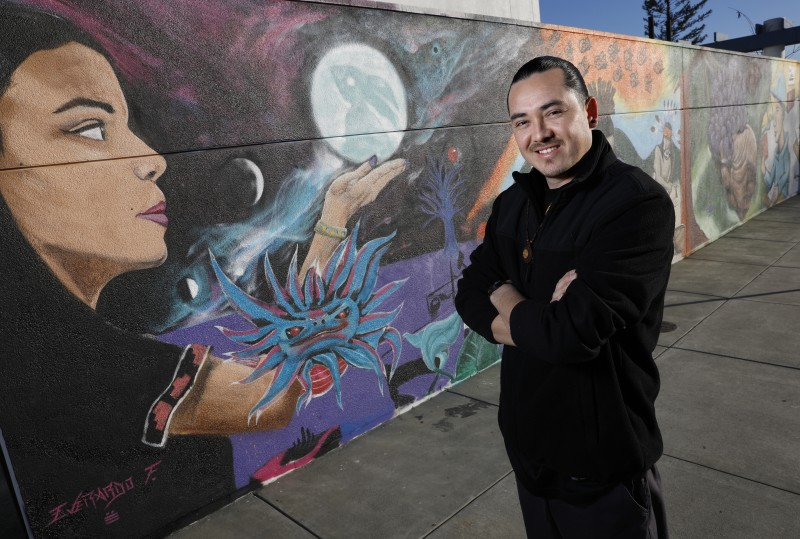 Emmanuel Morales is one of three artists that helped to create a mural celebrating diversity, native culture, and the immigrant experience on a wall which had been previously vandalized with pro-Trump sentiments. Photo taken at Cali Calmecac Language Academy on Friday, January 13, 2017 in Windsor, California . (BETH SCHLANKER/
