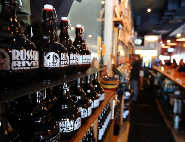 Growlers sit on a shelf behind the bar at Russian River Brewing Company, in Santa Rosa, on Wednesday, September 4, 2013. (Christopher Chung/ The Press Democrat)