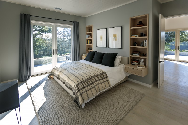 A sense of calm extends into the master bedroom with a soft color palette and cozy gable rug. Muscatine and Madhavan often have their morning coffee here, looking out the floor-to-ceiling windows.
