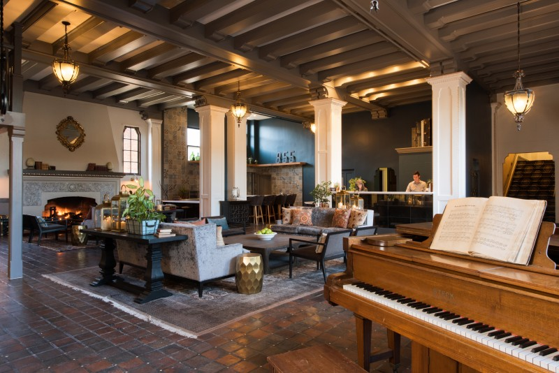 The hotel's spacious lobby has its original tile flooring and imposing fireplace, with an antique baby grand piano guests are welcome to play.