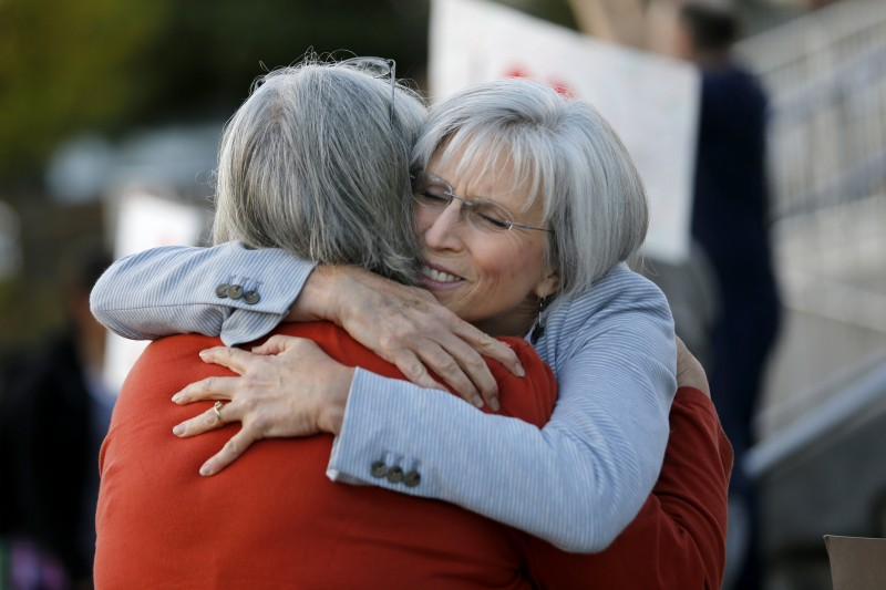 Principal Jeanne Acuña, right, hugs school librarian Gail Bland as community members show their support. (Beth Schlanker)