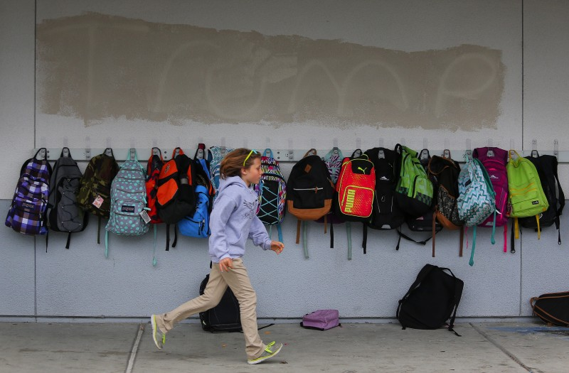 Fourth-grader Violet Meyer runs past the putlines of graffiti that had been covered over last October on the Cali Calmécac Language Academy Campus in Windsor. (Christopher Chung)