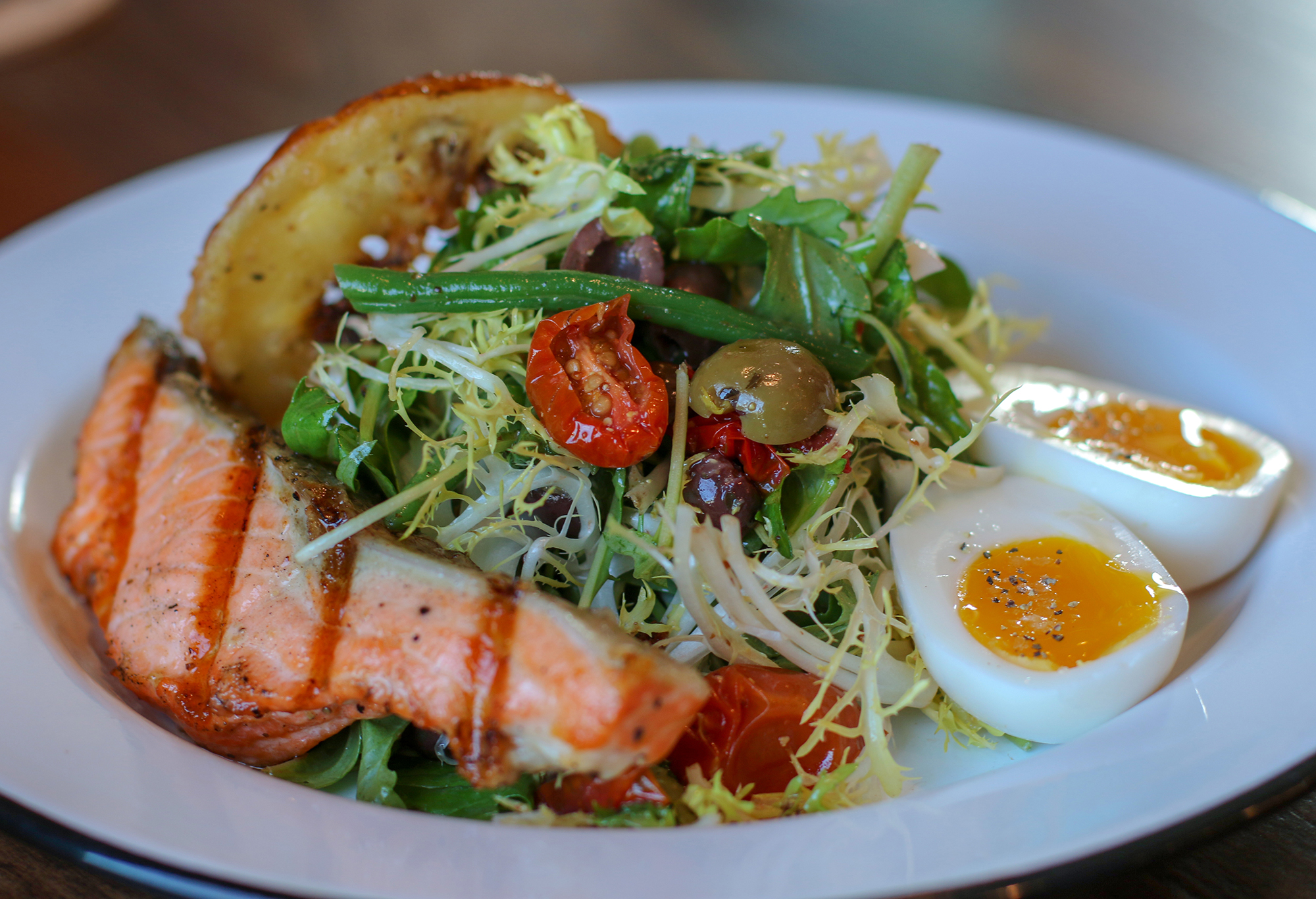 Grilled steelhead salad with chilled soft boiled egg, haricot vert, olives, frisee, mizuna, smoked tomato, meyer vinaigrette, tempura meyer lemon at Tips Roadside in Kenwood. Heather Irwin/PD