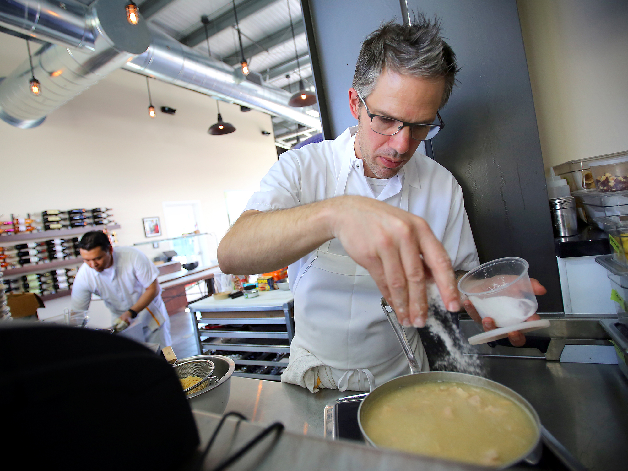 Mark Hopper, owner and chef at Vignette, puts salt in his casserole made from earthquake kit ingredients, in Sebastopol on Thursday, October 2, 2014. (Christopher Chung/ The Press Democrat)